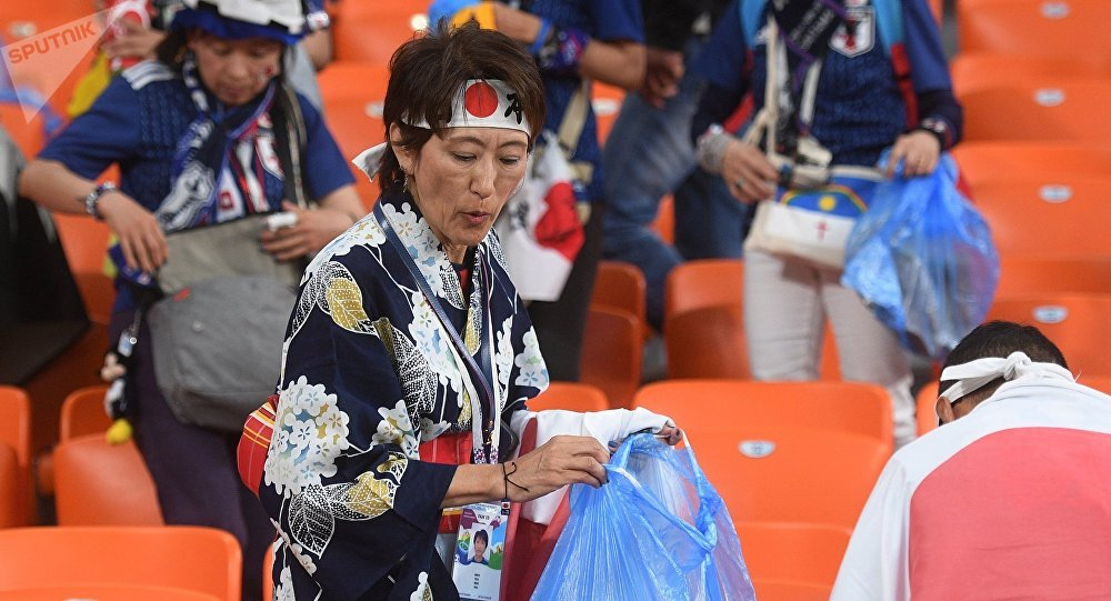Los hicnhas de Japón limpian el estadio tras el partido con Senegal