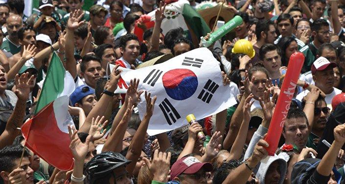 Hinchas mexicanos sostienen la bandera surcoreana en Ciudad de México