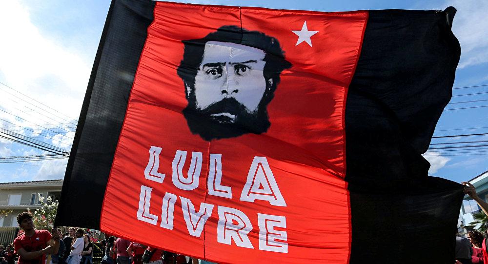 Partidarios del expresidente brasileño Luiz Inácio Lula da Silva sostienen una bandera junto al edificio de la Policía, en Curitiba