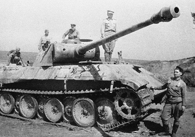 Soldados soviéticos cerca de un tanque alemán destruido en la batalla de Kursk
