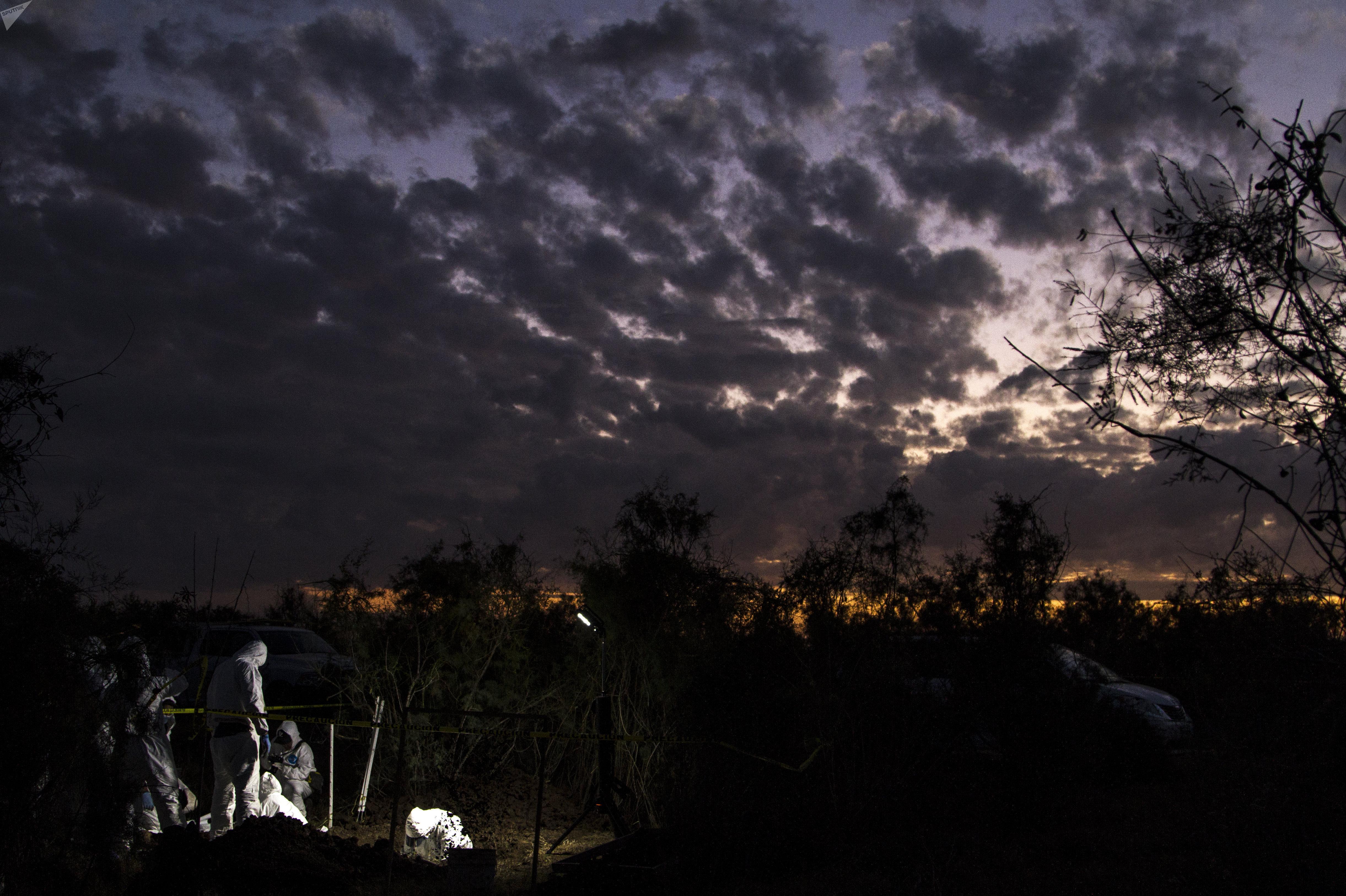Peritos de la Policía científica recogen un cráneo hallado por familiares en una fosa clandestina de Sinaloa, México