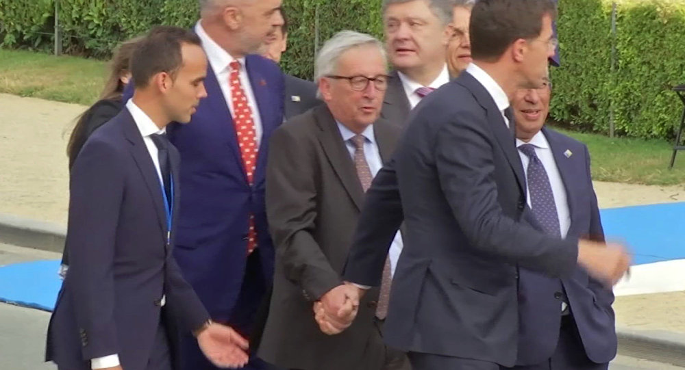 In this Wednesday, July 11, 2018 grab taken from video, European Union leader Jean-Claude Juncker is helped by Netherlands Prime Minister Mark Rutte at Brussels Parc Cinquantenaire, in Brussels, Belgium.