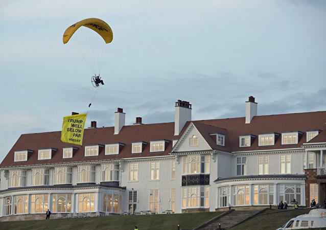 Un activista de Greenpeace con la pancarta 'Trump está muy por debajo de la media' pasa por el hotel en el que reside el presidente estadounidense en Escocia el 14 de julio