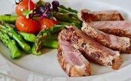 Un plato con carne y espárragos