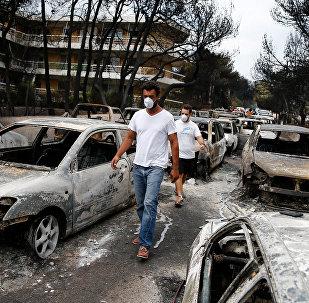 Dos hombres caminan entre autos calcinados después del incendio forestal en Grecia
