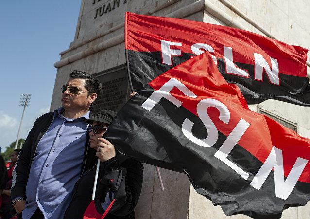 Sandinista porta las banderas del FSLN en el 39 Aniversario de la Revolución nicaraguense