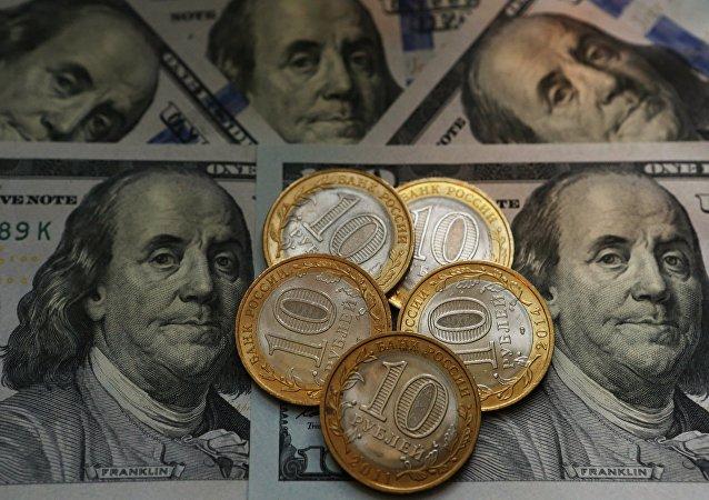 Monedas de rúblos rusos y billetes de dólares estadounidenses