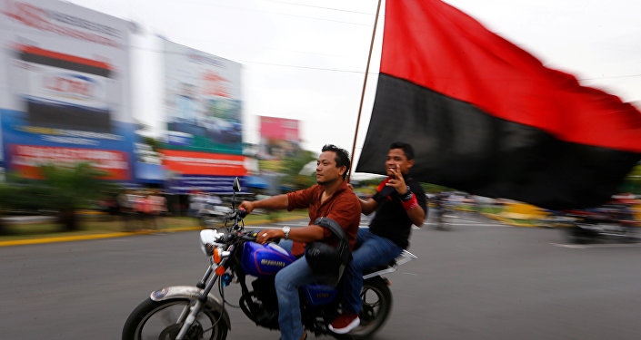 Dos motociclistas con una bandera del Frente Sandinista de Liberación Nacional de Nicaragua.