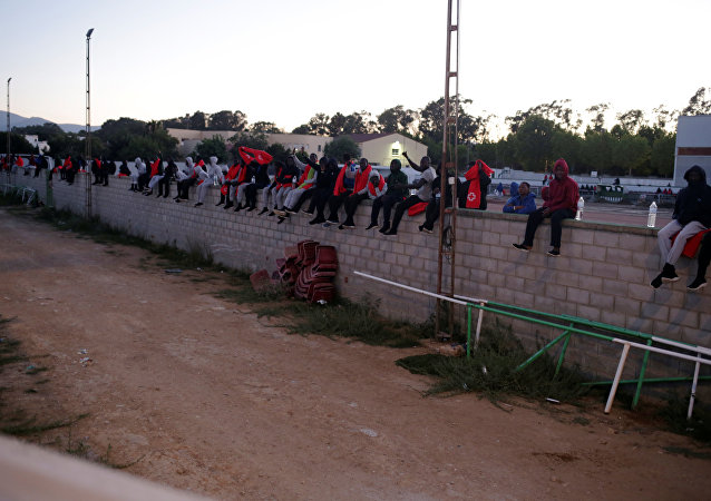 Los migrantes sentados en un muro, España
