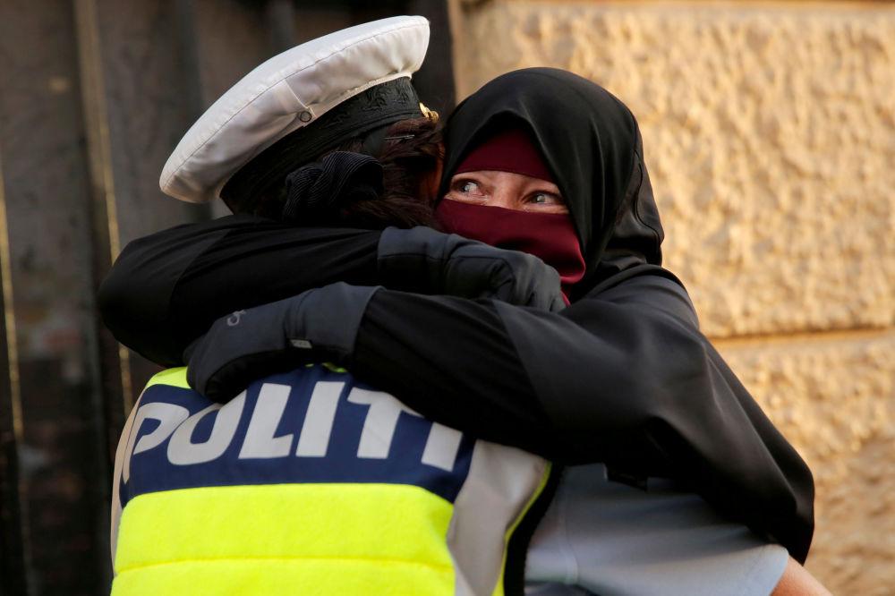 Una mujer y un policía se abrazan durante una manifestación de protesta por la entrada en vigor de la prohibición del burka en Dinamarca.