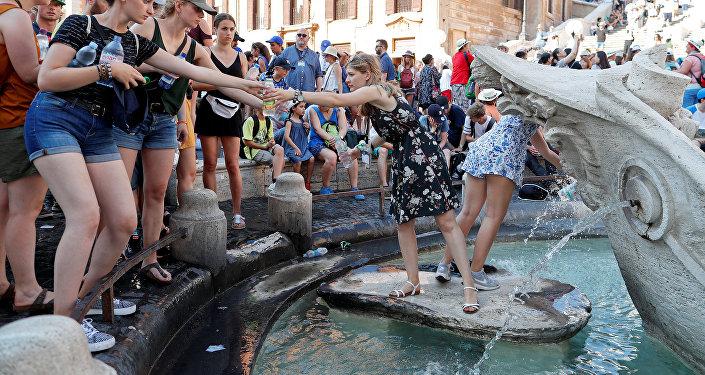 La gente llenando las botellas con agua en una fuente de Roma, Italia
