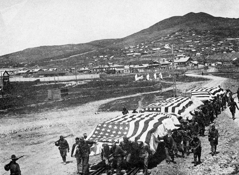Los invasores estadounidenses llevan plataformas con los fallecidos durante los combates en el Lejano Oriente para su envío a Estados Unidos