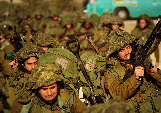 Soldados israelíes caminan hacia el norte de la Franja de Gaza desde la frontera israelí con Gaza
