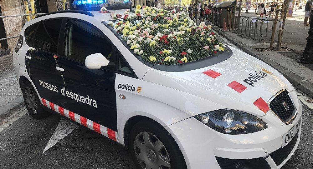 Un vehículo de los Mossos d'Esquadra cortando el acceso a una manifestación a favor del referéndum. La gente decoró el auto con claveles en señal de solidaridad.