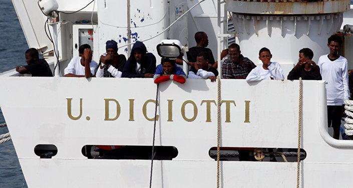 Los migrantes esperan para desembarcar del barco de la guardia costera italiana Diciotti