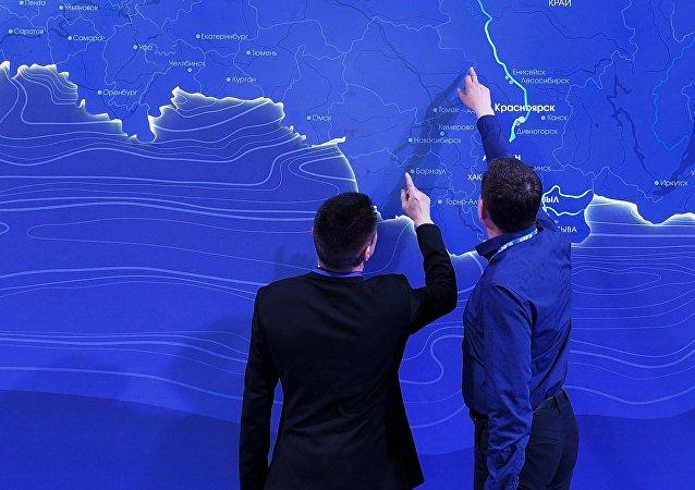 Hombres observando el mapa de Rusia en el Foro Económico de Krasnoyarsk (archivo)