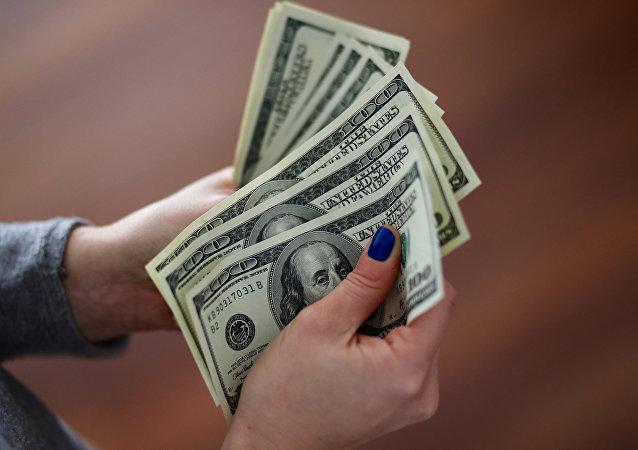 Una mujer cuenta los billetes de un dólar