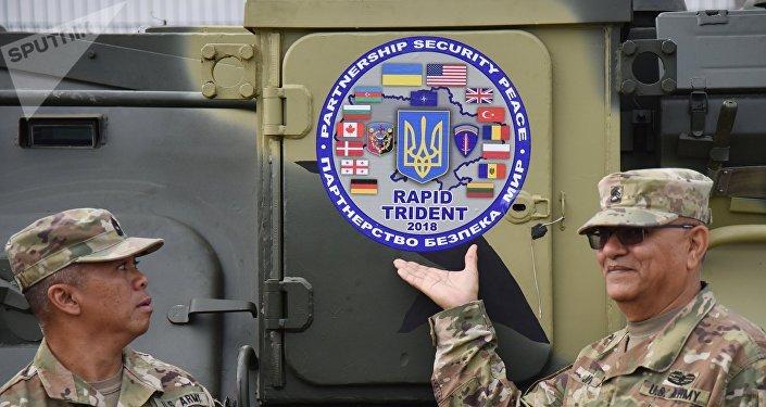 Militares junto con logo de los ejercicios militares Rapid Trident 2018