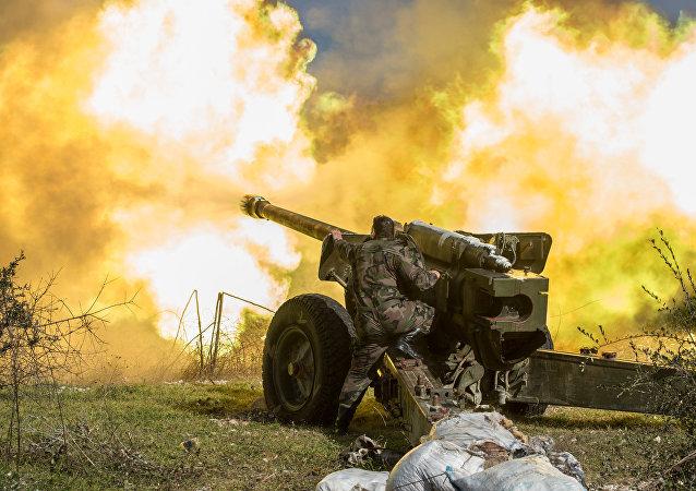 Un soldado sirio dispara de una pieza de artilleria en Idlib