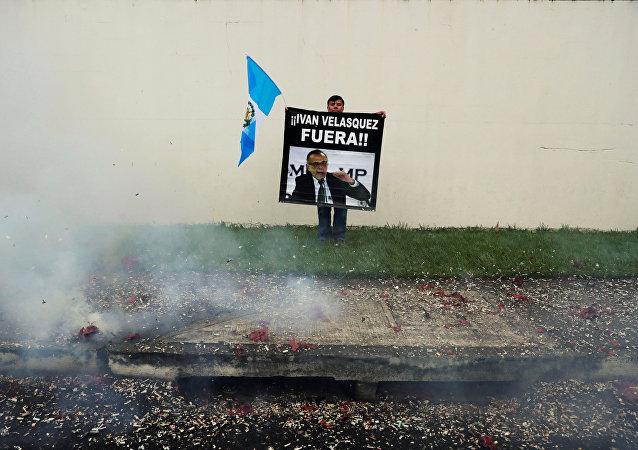 Un manifestante sostiene un cartel frente a la sede de la CICIG en Guatemala