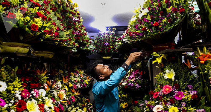 Moisés acomoda un arreglo floral en el mercado Jamaica Vive