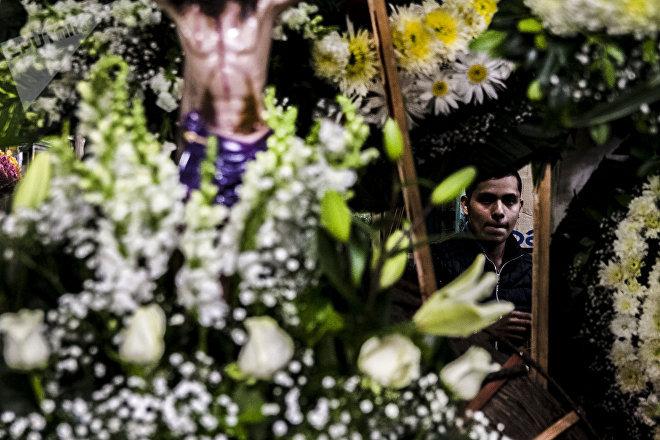 Vendedor tras un arreglo de flores funerario en el mercado Jamaica Vive