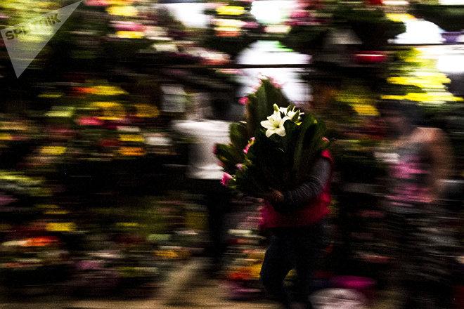 Una mujer lleva y trae arreglos florales para una marchanta