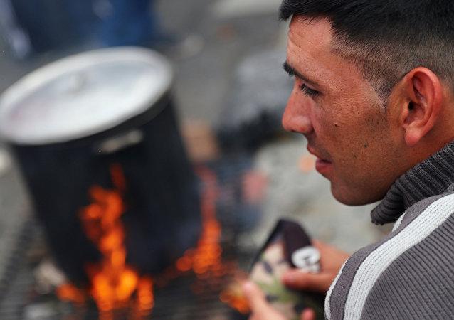 Un hombre espera por un plato de comida en una olla popular en Buenos Aires.