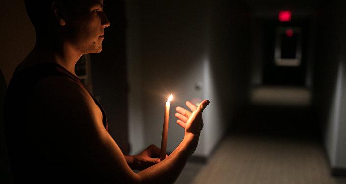 Hombre con una vela durante el huracán Florence