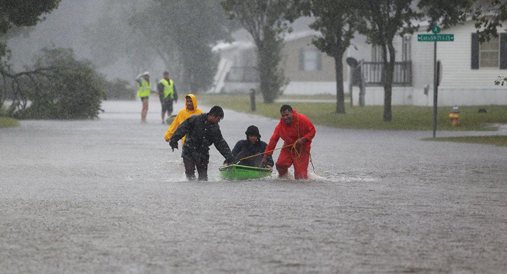 Vecinos ayudan a un anciano a evacuar una comunidad en Carolina del Norte durante el huracán Florence