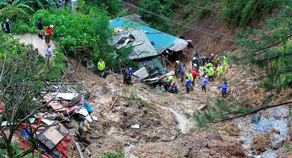 Unos rescatistas buscan a tres ciudadanos enterrados por un deslizamiento durante el tifón Mangkhut