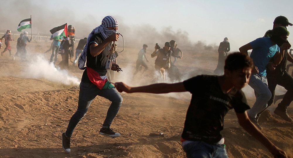 Palestinos huyen del gas lacrimógeno disparado por las tropas israelíes durante una protesta en la Franja de Gaza