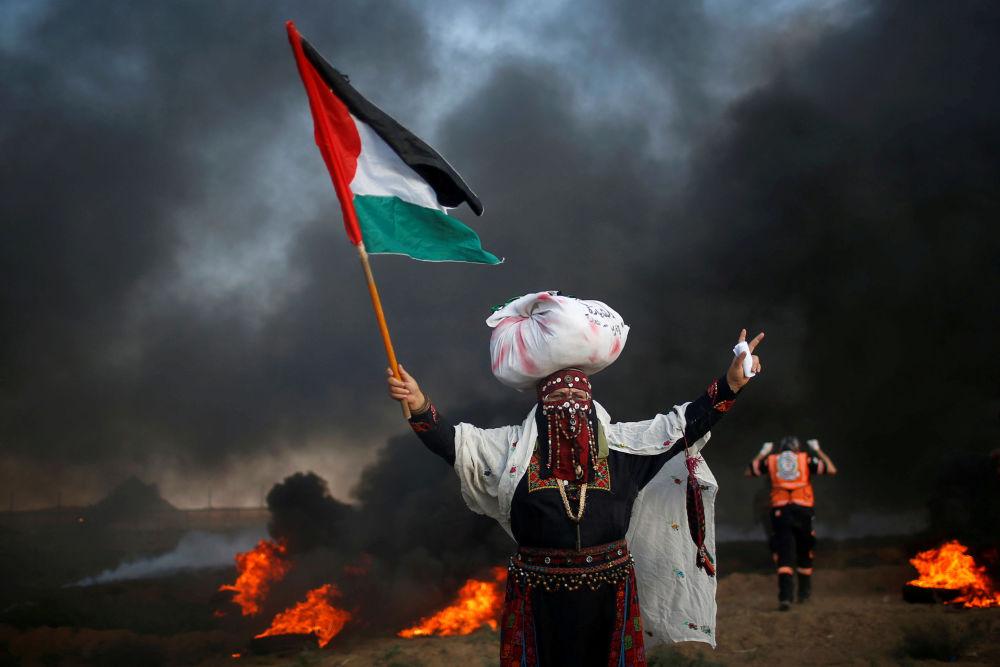 Una mujer con la bandera de Palestina, durante una manifestación al lado de la frontera con Israel.