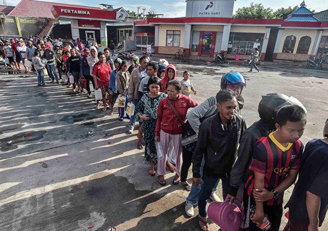 La gente hace cola para obtener combustible en una gasolinera tras el terremoto y tsunami en Indonesia