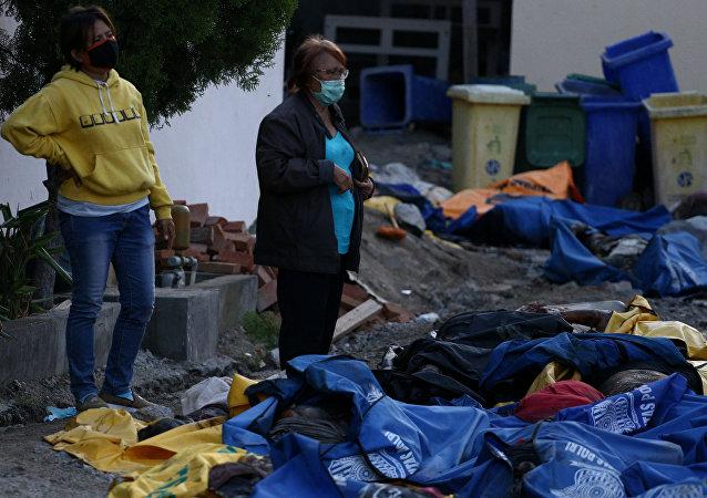 Residentes de Indonesia examinan las víctimas tras el tsunami