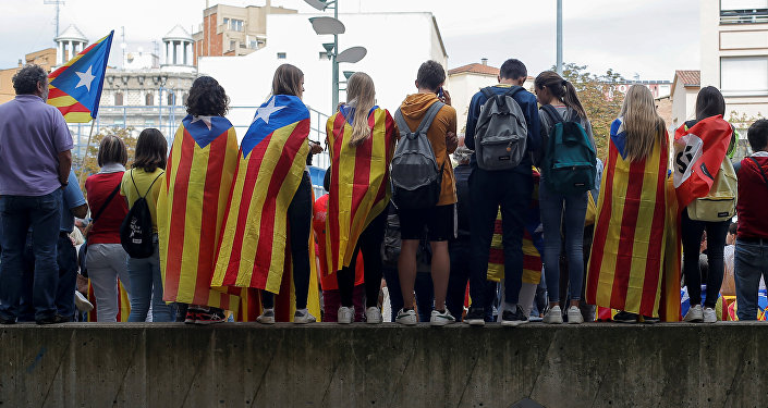 Las personas usan la bandera independista de Cataluña durante el primer aniversario del referéndum