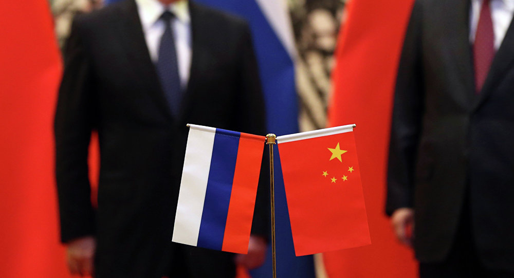 The Russian and Chinese national flags are seen on the table as Russia's President Vladimir Putin (back L) and his China's President Xi Jinping (back R) stand during a signing ceremony at the Diaoyutai State Guesthouse in Beijing on November 9, 2014