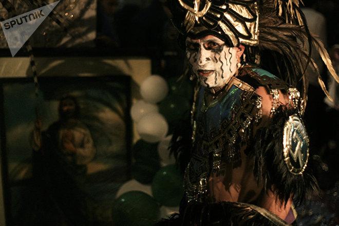 Danzante con traje prehispánico ofrece limpias frente a un cuadro de San Judas Tadeo en el Templo de San Hipólito en la Ciudad de México