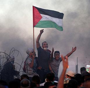 Unos jóvenes con la bandera palestina en las protestas en la frontera con Israel