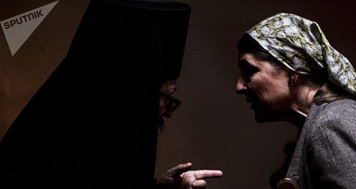 Miembro de Iglesia Ortodoxa Rusa habla con una de las fieles durante uno de los oficios religioso
