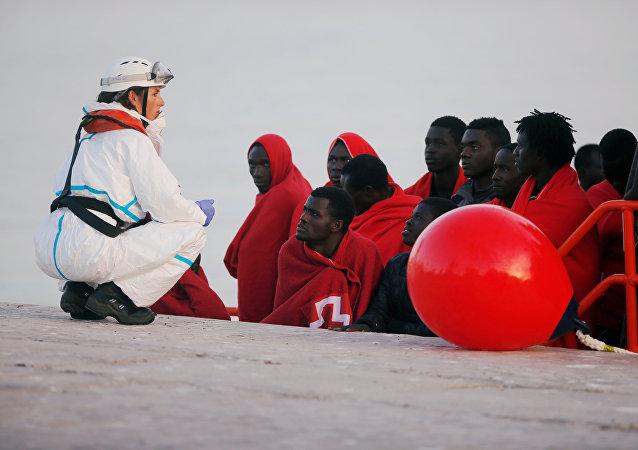 Migrantes desembarcan del barco de rescate en un puerto español