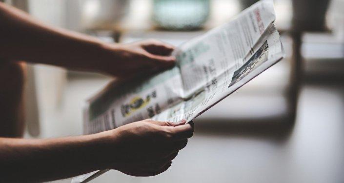 Una persona con un periódico en las manos