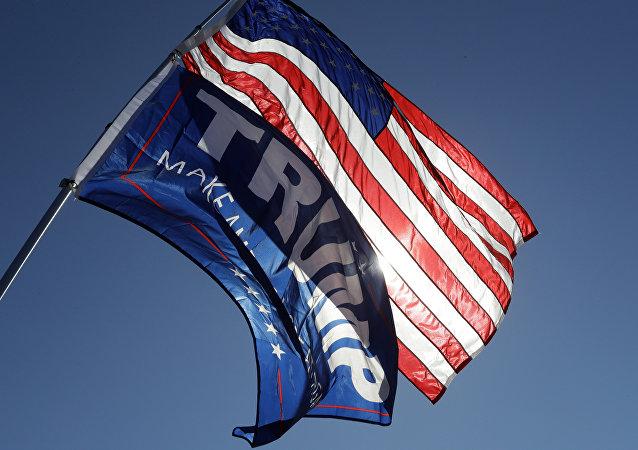 Un partidario del candidato presidencial republicano Donald Trump sostiene la bandera estadounidense y una bandera de campaña de Trump