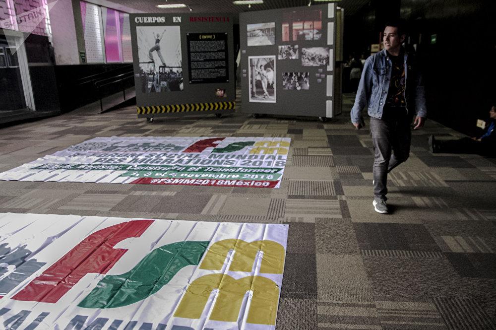 Un joven camina frente a una manta con el logotipo del 8° Foro Social Mundial de las Migraciones en México.