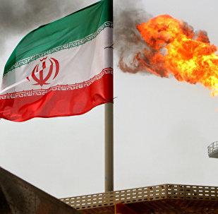 La bandera de Irán con una llama de gas en una plataforma de producción de petróleo a fondo