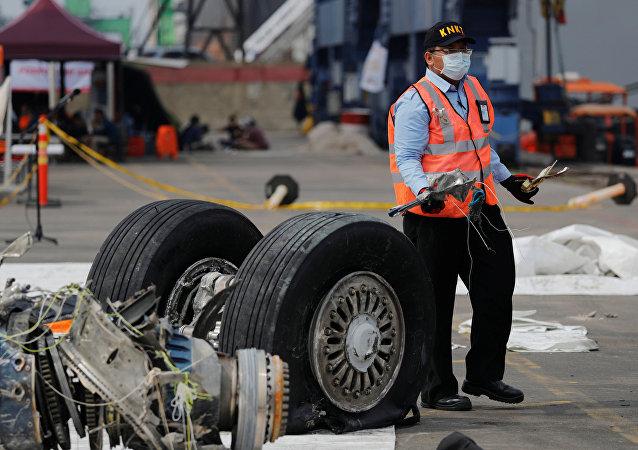 Un funcionario de la Comisión Nacional de Seguridad del Transporte de Indonesia transporta escombros del vuelo JT610 de Lion Air, Indonesia