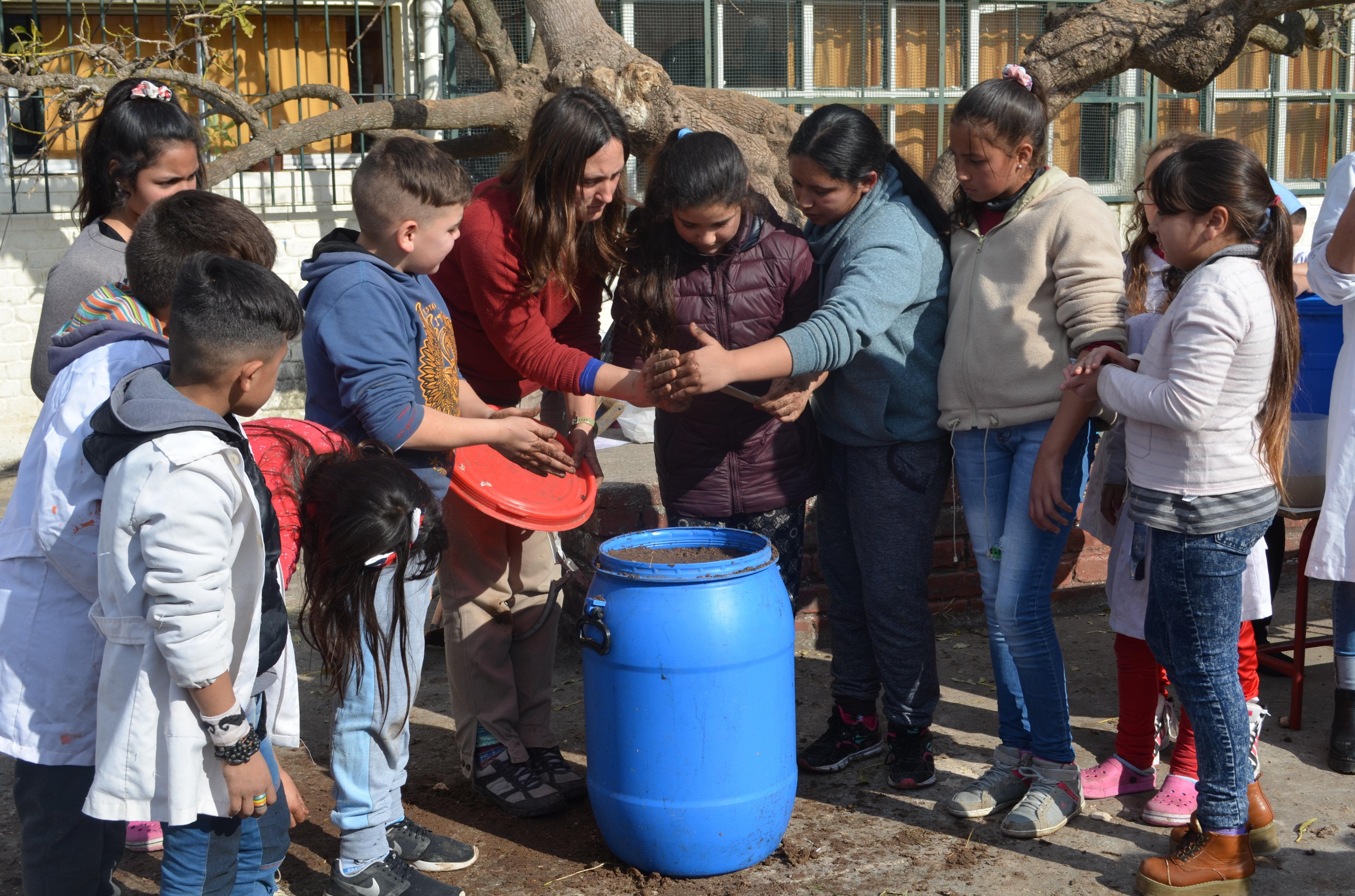 Alumnos del proyecto Entre bichitos preparando los Microorganismos Eficientes Nativos en la escuela montevideana República Popular China