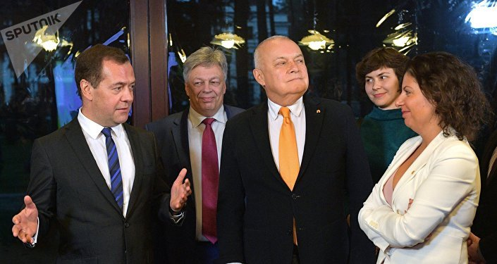 El primer ministro ruso, Dmitri Medvédev, reunido con el jefe de Rossiya Segodnya, Dmitri Kiseliov y la directora de Sputnik, Margarita Simonián, en el concurso internacional de fotoperiodismo Stenin.
