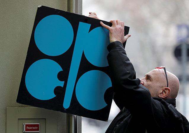 Un hombre coloca un cartel con el logotipo de la OPEP junto a la entrada de su sede antes de una reunión de ministros de petróleo de la OPEP en Viena