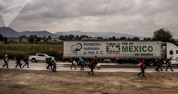 """Hidalgo. Camión con la leyenda """"por un México sin hambre"""" pasa frente a la caravana de centroamericanos que camina rumbo a Querétaro para descansar y seguir su camino a EEUU"""